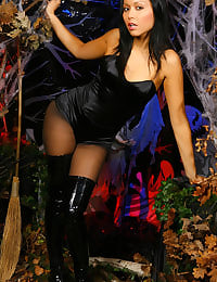 Stunning Lily S is ready for Halloween wearing a sexy witch's outfit; a short black dress with pantyhose and long black leather boots