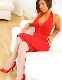 Sexy busty brunette in red dress and white stockings.