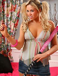 Cute blonde with pigtails fools around in her bedroom in her denim miniskirt.