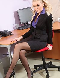 Porchia W in a smart black skirt suit and heels.