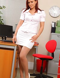 Kinky redhead teases her way out of her work clothes and poses over her desk.