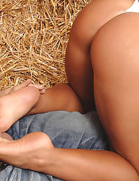 Babe gives footjob in the hay
