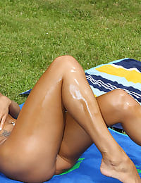 Ashley Bulgari Oils Up in the Sun with her shaved pussy