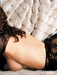 Ginger Jolie in Laying in furs in black top and skirt