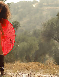 a brunette young girl nude in nature carrying a red umbrella and playing with a big cucumber