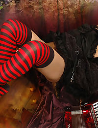 gothic chick wearing long striped socks, plays with her pussy lips and metal pinces and pee play