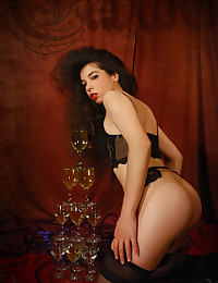 Idoia in black lingerie makes a burlesque show with a black dildo and after she piss in a champagne glasses tower